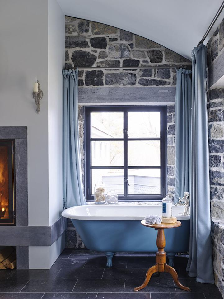 <p>Rustic doesn't necessarily mean the opposite of sophisticated. Case in point: this bathroom. In fact, the exposed stone walls make it feel like a master bathroom fit for a queen. The traditional wooden stool and ornate sconces contribute to that old-world look while the fresh blue paint and matching curtains keep things contemporary. </p>