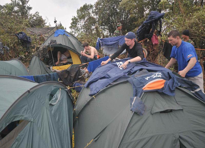Russian rescuers dry clothes on their tents near the site where a Sukhoi Superjet-100 crashed, on the peak of Mount Salak, West Java, Indonesia, Tuesday, May 15, 2012. Joint teams of Indonesian and Russian experts continued to comb through debris at the bottom of a 1,500-foot (500-meter) ravine on Tuesday afternoon to find the black box of the new passenger jet with 45 people on board that slammed into a cliff atop the dormant Indonesian volcano last week. (AP Photo/Jefri Tarigan)
