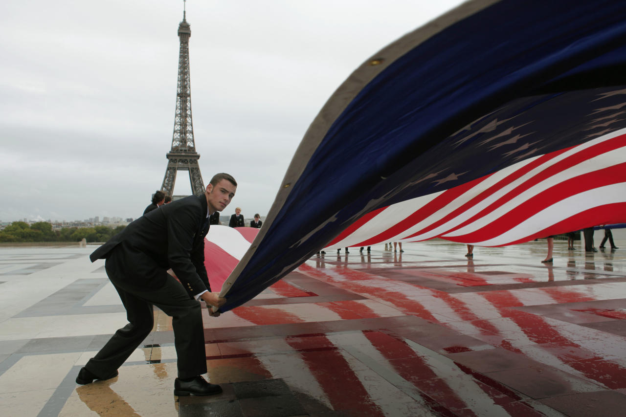 An American flag is unfurled  during a commemoration to mark the 10th anniversary of the Sept. 11 attacks on the United States, at the Trocadero plaza , near the Eiffel tower, seen in the background, in Paris, Sunday, Sept. 11, 2011. (AP Photo/Thibault Camus)
