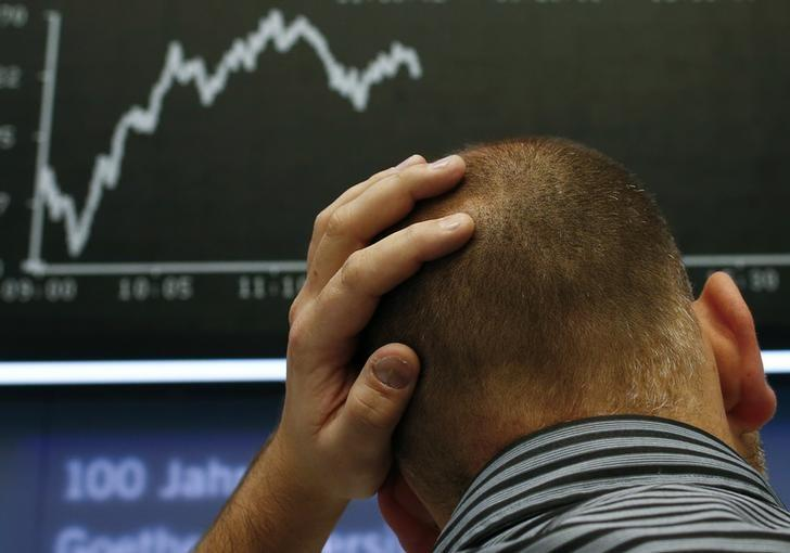 A trader stands under the DAX index board at Frankfurt stock exchange