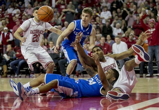 Arkansas' Coty Clarke (4) fights for the ball under the basket against Kentucky's Julius Mays (34) during the first half of an NCAA college basketball game in Fayetteville, Ark., Saturday, March 2, 2013. (AP Photo/Gareth Patterson)