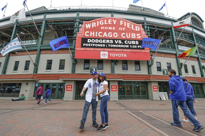 CORRECTS YEAR TO 2021-Los Angeles Dodgers fans Carlos Cativo and Nicole Ramos pose for a picture outside the Wrigley Field as a baseball game between the Chicago Cubs and Los Angels Dodgers has been postponed due to the forecast of inclement weather, Monday, May 3, 2021, in Chicago. (AP Photo/Kamil Krzaczynski)