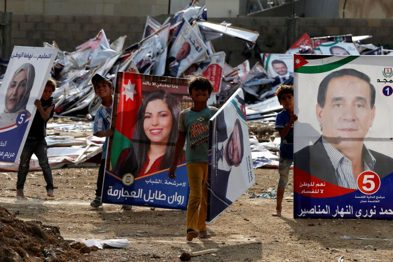 Children pose as they search for wood in parliamentary candidates' posters after parliament elections results were announced in Amman