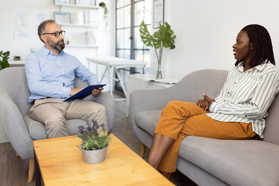 Young African-american mother talking with a male psychologist about her daughter´s problems.