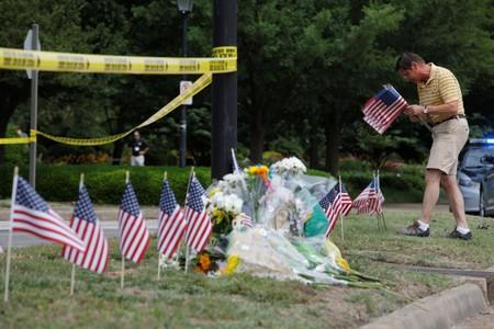 Local resident Rich Lindgren places flags at a makeshift memorial outside a municipal government building where a shooting incident occurred in Virginia Beach, Virginia