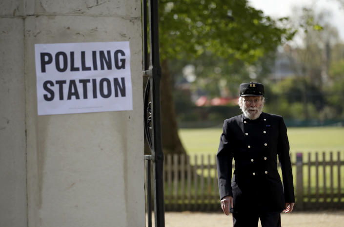 A Chelsea Pensioner walks past a sign for a polling station after voting in London, Thursday, May 6, 2021. Millions of people across Britain will cast a ballot on Thursday, in local elections, the biggest set of votes since the 2019 general election. A Westminster special-election is also taking place in Hartlepool, England. (AP Photo/Matt Dunham)