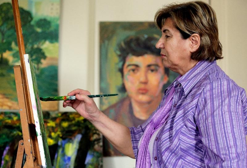 Mariam Saidi paints as she stands in front of an oil painting of her son Maher (centre-background), who disappeared in 1982 at the age of 15 while fighting near Beirut, at her house in the Lebanese capital on April 8, 2015 (AFP Photo/Joseph Eid)