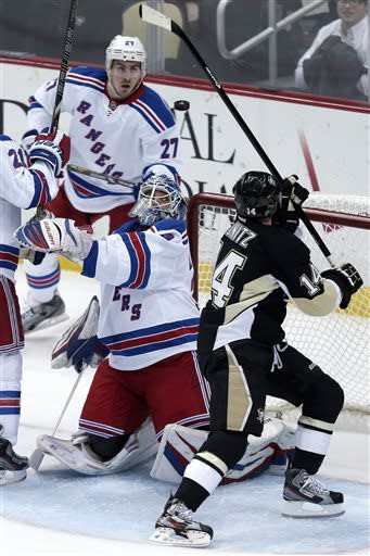 New York Rangers goalie Henrik Lundqvist (30) keeps his eye on a bounding puck with Pittsburgh Penguins left wing Chris Kunitz (14) attempting to do the same during the first period of an NHL hockey game in Pittsburgh on Friday, April 5, 2013. (AP Photo/Gene J. Puskar)