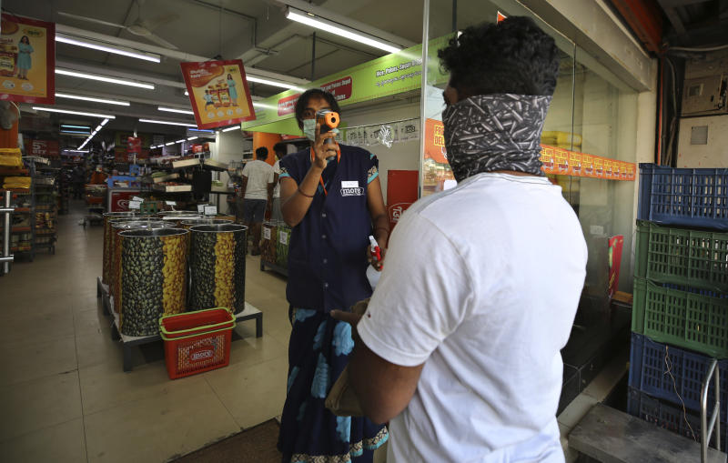 An Indian attendant checks the temperature of a customer before allowing him inside a supermarket during lockdown in Bangalore, India, Thursday, March 26, 2020. The unprecedented lockdown keeping India's 1.3 billion people at home for all but essential trips to places like supermarkets or pharmacies is meant to keep virus cases from surging above the 553 already recorded and overwhelming an already strained health care system. The new coronavirus causes mild or moderate symptoms for most people, but for some, especially older adults and people with existing health problems, it can cause more severe illness or death. (AP Photo/Aijaz Rahi)