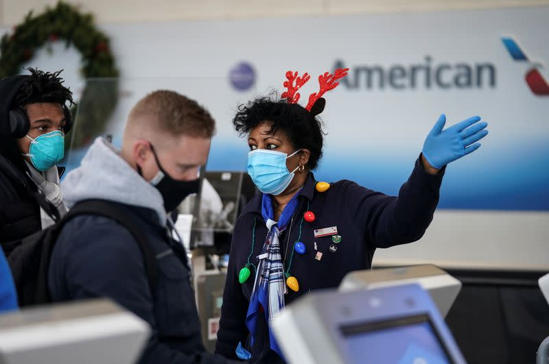An airline worker in Christmas themed attire assists travelers at Ronald Reagan Washington National Airport in Arlington, Virginia