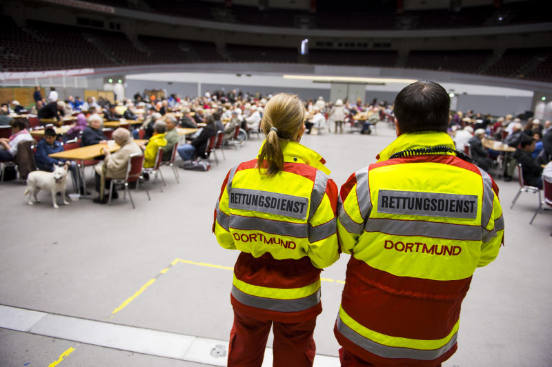 Rescue workers watch evacuated persons in the Westfalen Halle hall in Dortmund, Germany, Sunday Nov. 3, 2013. More than 20,000 people are being evacuated from their homes in the west German city of Dortmund as authorities prepare to defuse a massive bomb left over from World War II. The 4,000-pound (1,800-kilogram) bomb was discovered after experts analyzed old aerial photographs while searching for unexploded ordnance dropped by Allied aircraft over Germany's industrial Ruhr region. (AP Photo/dpa,Marcus Simaitis)