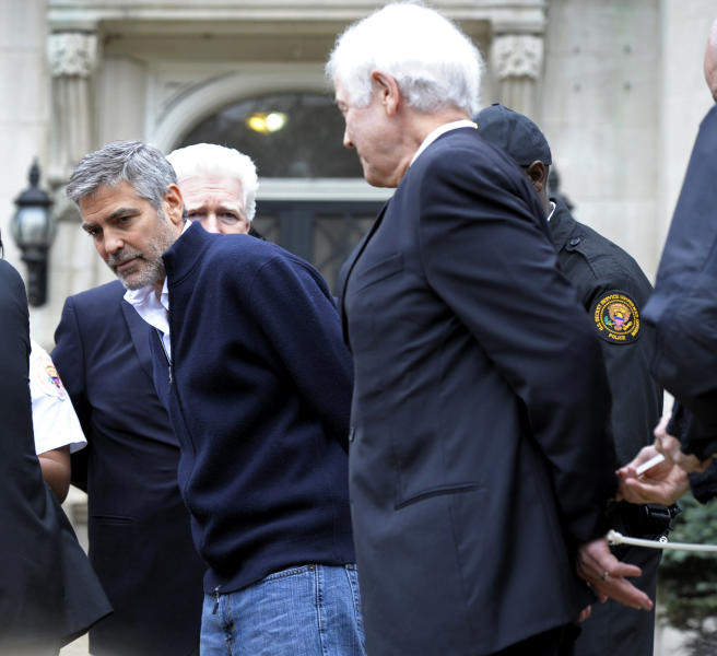 Actor George Clooney, center, Rep. Jim Moran, D-Va, back, and Clooney's father, Nick Clooney, right, are arrested during a protest at the Sudanese Embassy in Washington, Friday, March 16, 2012. The demonstrators are protesting the escalating humanitarian emergency in Sudan that threatens the lives of 500,000 people. (AP Photo/Cliff Owen)