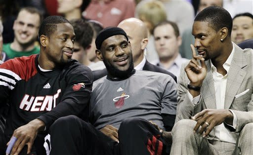 From left, Miami Heat's Dwyane Wade, LeBron James and Chris Bosh joke around on the bench during the first minutes of an NBA basketball game against the Boston Celtics in Boston, Tuesday, April 24, 2012. (AP Photo/Elise Amendola)