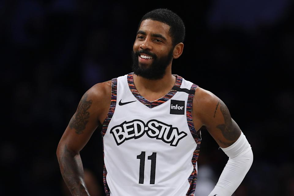 Kyrie Irving with a slight smile and his hands on his hips during a game.