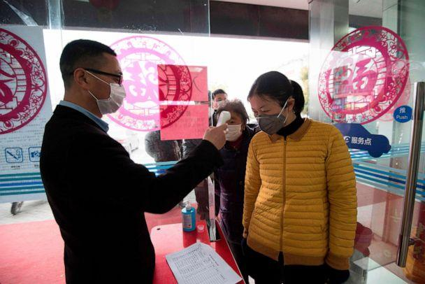 PHOTO: This photo taken on Feb. 25, 2020, shows a customer having her temperature taken at the entrance to a bank in Nantong, in China's eastern Jiangsu province, as the country is hit by an outbreak of the novel coronavirus. (Str/AFP via Getty Images)