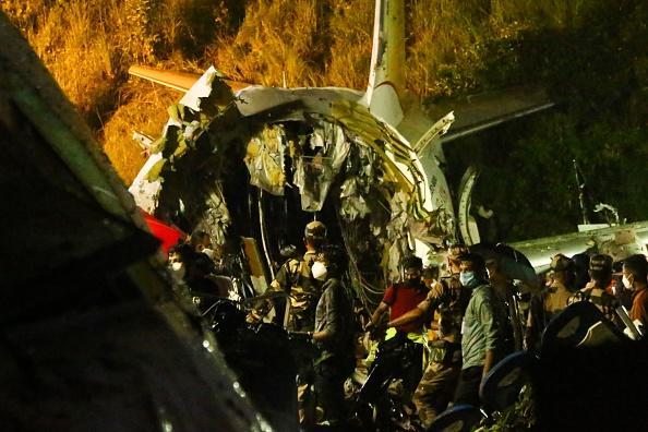 First responders inspect the wreckage of an Air India Express jet, which was carrying more than 190 passengers and crew from Dubai, after it crashed by overshooting the runway at Calicut International Airport in Karipur, Kerala.