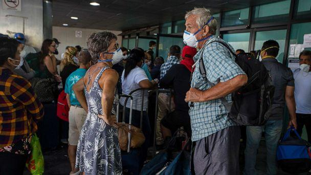 PHOTO: Travelers wait for a charter flight coordinated by the U.S. embassy at the La Aurora airport in Guatemala City, Tuesday, March 24, 2020. (Moises Castillo/AP)