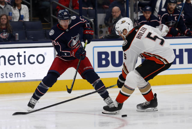 Columbus Blue Jackets forward Riley Nash, left, passes the puck next to Anaheim Ducks defenseman Korbinian Holzer, of Germany, during the second period of an NHL hockey game in Columbus, Ohio, Friday, Oct. 11, 2019. (AP Photo/Paul Vernon)