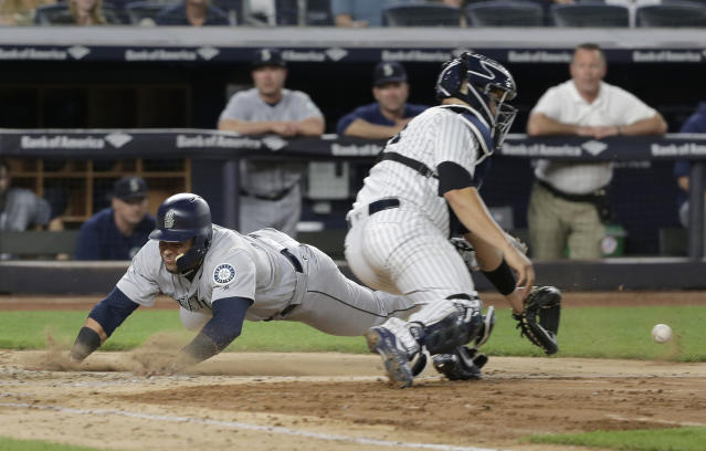 Seattle Mariners' Nelson Cruz, left, slides home to score past New York Yankees catcher Gary Sanchez during the fifth inning of a baseball game at Yankee Stadium on Wednesday, June 20, 2018, in New York. (AP Photo/Seth Wenig)
