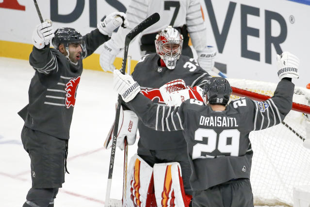 Calgary Flames goalie David Rittich (33) celebrates with Calgary Flames defender Mark Giordano, left, and Edmonton Oilers forward Leon Draisaitl (29) after the Pacific Division defeated the Atlantic Division 5-4 in the NHL hockey All Star final game Saturday, Jan. 25, 2020, in St. Louis. (AP Photo/Scott Kane)