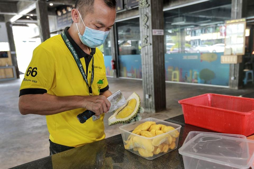 A worker fills a plastic container with durian in Petaling Jaya June 8, 2020. — Picture by Ahmad Zamzahuri