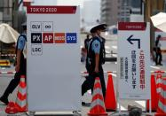 Police officers patrol at the entrance of the Athletes Village ahead of Tokyo 2020 Olympic Games in Tokyo