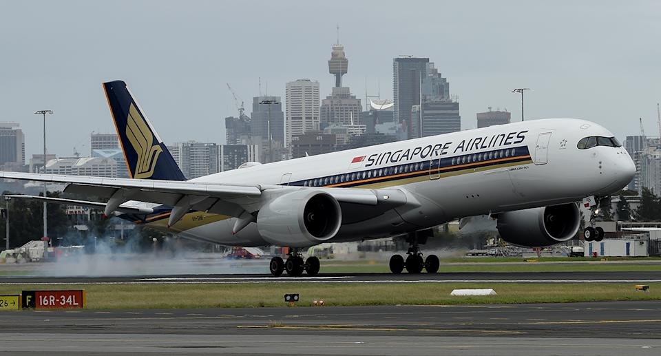 A Singapore Airlines flight touches down at Sydney International Airport.