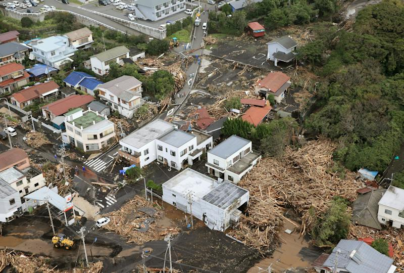 Several houses in a residential area in Oshima are covered by debris of mudslides after a powerful typhoon hit Izu Oshima island, about 120 kilometers (75 miles) south of Tokyo Wednesday morning, Oct. 16, 2013. Typhoon Wipha has lashed Japan, leaving at least seven people dead on a Pacific island south of Tokyo as it cut across the capital region and headed north. (AP Photo/Kyodo News) JAPAN OUT, CREDIT MANDATORY