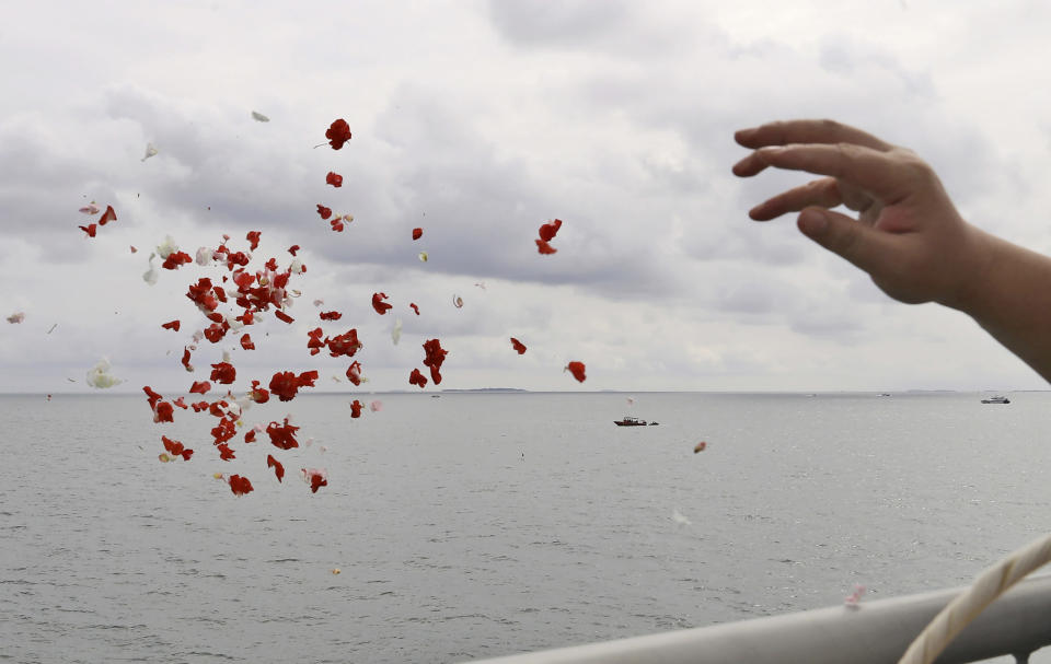 A relative throws flowers into the Java Sea where Sriwijaya Air flight SJ-182 crashed on Jan. 9 killing all of its passengers, during a memorial ceremony held on deck of Indonesian Navy Ship KRI Semarang, near Jakarta in Indonesia, Friday, Jan. 22, 2021. (AP Photo/Tatan Syuflana)