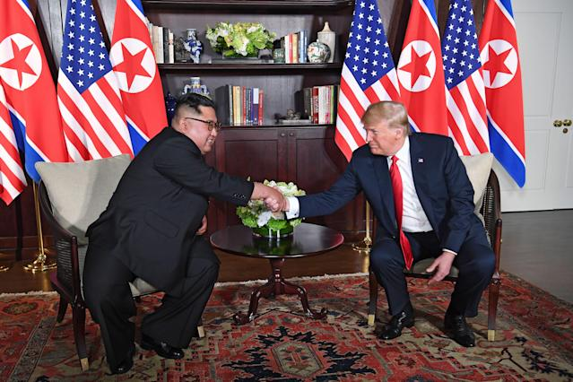 <p>US President Donald Trump (R) shakes hands with North Korea's leader Kim Jong Un (L) as they sit down for their historic US-North Korea summit, at the Capella Hotel on Sentosa island in Singapore on June 12, 2018. – Donald Trump and Kim Jong Un have become on June 12 the first sitting US and North Korean leaders to meet, shake hands and negotiate to end a decades-old nuclear stand-off. (Photo: Saul Loeb/AFP/Getty Images) </p>