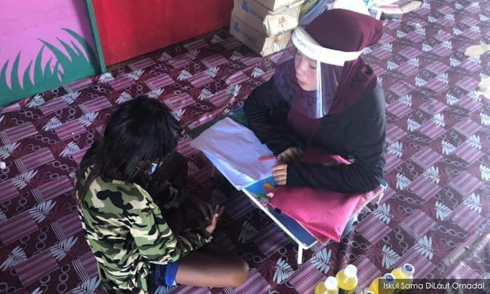 Enidah teaching one of the students