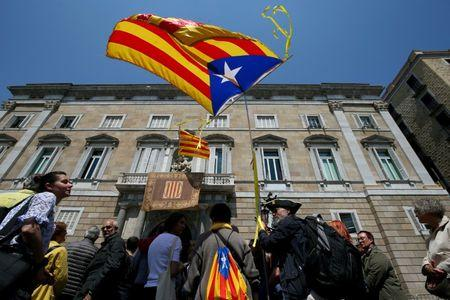 """FILE PHOTO: A man waves an """"Estelada"""", Catalan separatist flag, outside the Generalitat Palace in Barcelona, Spain, May 17, 2018. REUTERS/Albert Gea"""