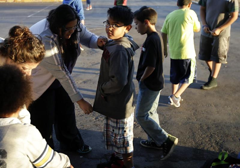 In this March 14, 2014 picture, Marina Beltran, left, zips up the jacket of her son Antonio before he takes part in an early morning running program at his elementary school in Chula Vista, Calif. Amid alarming national statistics showing an epidemic in childhood obesity, hundreds of thousands of students across the country are being weighed and measured. Beltran son's Chula Vista Elementary School District is being touted as a model for its methods that have resulted in motivating the community to take action. (AP Photo/Gregory Bull)