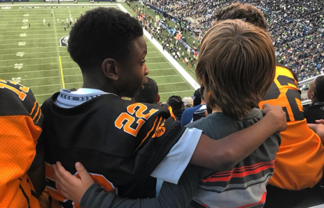 8-year-old Donovan Shaw puts his arm around a young boy who was waiting for his father at the Seattle Seahawks pre-season game against the Oakland Raiders. (Photo: Chelsea Burke via Facebook)
