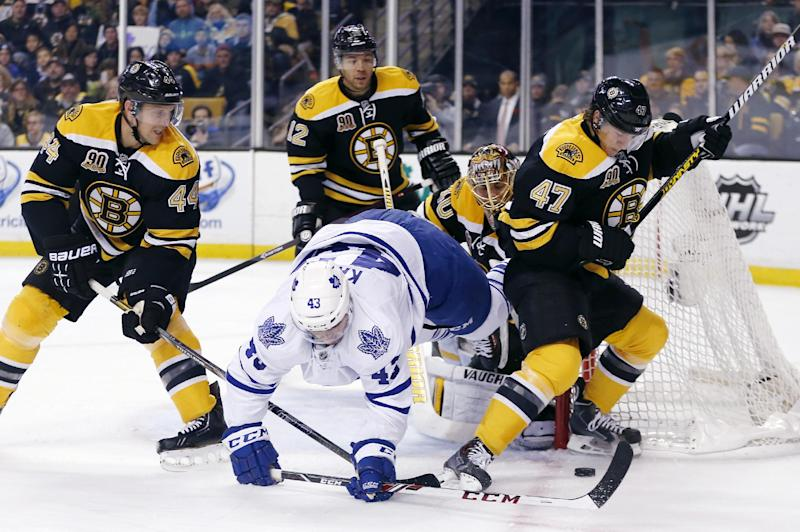 Toronto Maple Leafs' Nazem Kadri (43) falls while battling Boston Bruins' Torey Krug (47) and Dennis Seidenberg (44), of Germany, for the puck in the first period of an NHL hockey game in Boston, Saturday, Nov. 9, 2013. (AP Photo/Michael Dwyer)
