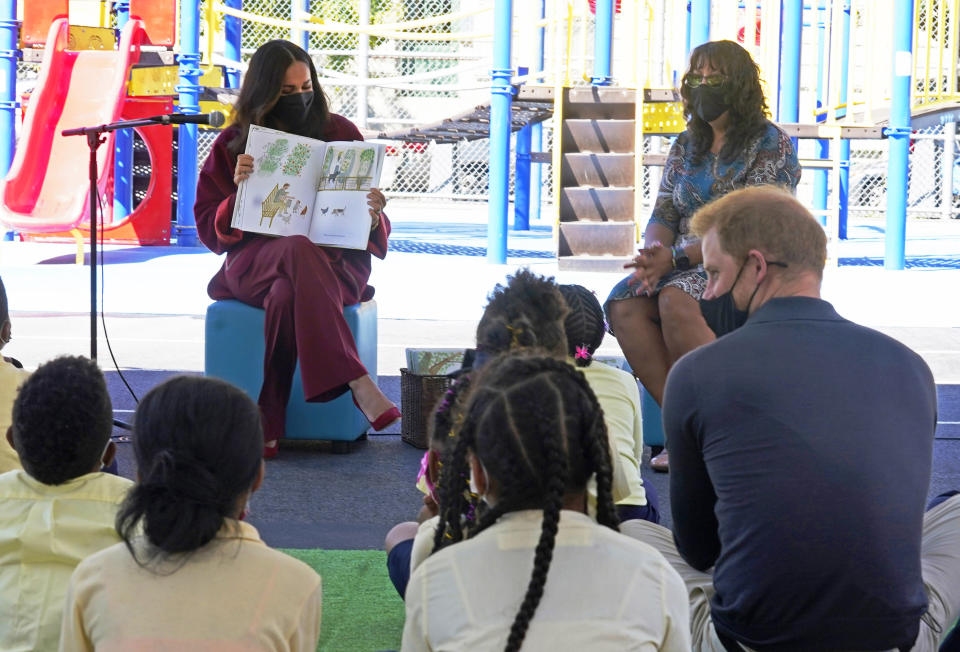 """Meghan, the Duchess of Sussex, reads from her book """"The Bench,"""" as Prince Harry, the Duke of Sussex, foreground right, and second grade students listen, during their visit to P.S. 123, the Mahalia Jackson School, in New York's Harlem neighborhood, Friday, Sept. 24, 2021. Seated background right is Principal Melitina Hernandez. (AP Photo/Richard Drew)"""