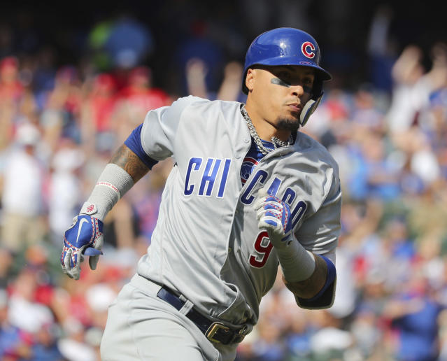 Chicago Cubs' Javier Baez (9) runs to first after hitting a three-run home run against the Texas Rangers in the fifth inning of a baseball game Thursday, March 28, 2019, in Arlington, Texas. (AP Photo/ Richard W. Rodriguez)