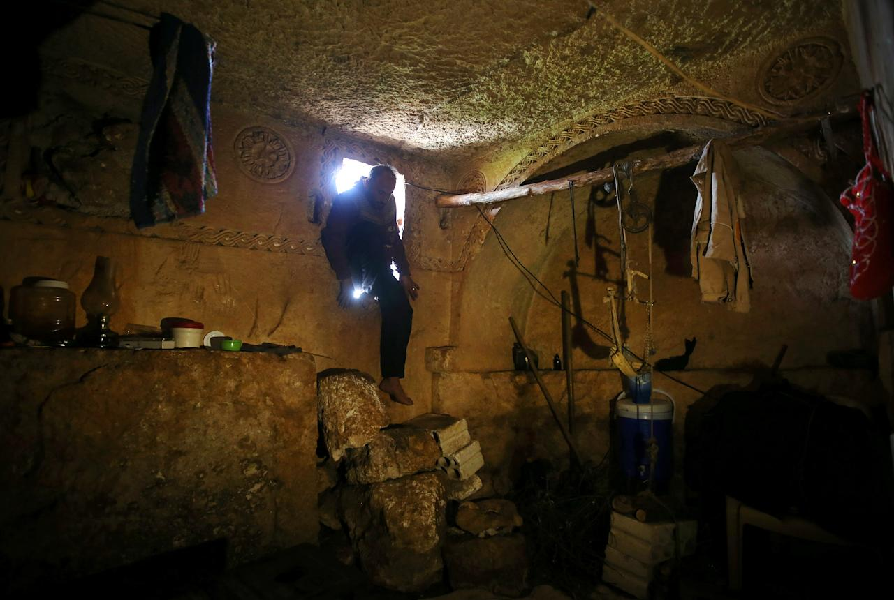 Sami, 32, steps into an underground Roman tomb used for shelter from Syrian government forces shelling and airstrikes, at Jabal al-Zaweya, in Idlib province, Syria, Thursday, Feb. 28, 2013. Across northern Syria, rebels, soldiers, and civilians are making use of the country's wealth of ancient and medieval antiquities to protect themselves from Syria's two-year-old war. They are built of thick stone that has already withstood centuries, and are often located in strategic locations overlooking towns and roads. (AP Photo/Hussein Malla)