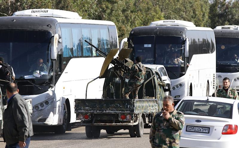 Members of the Syrian government forces escort buses carrying Syrians as hundreds of civilians and Syrian rebel forces began evacuating the last opposition-held district of Waer in Homs, under a deal with the Syrian regime, on December 9, 2015 (AFP Photo/Louai Beshara)