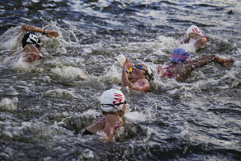 Samantha Arevalo, center, of Ecuador, takes a drink at a feeding station during the women's marathon swimming event at the 2020 Summer Olympics, Wednesday, Aug. 4, 2021, in Tokyo, Japan. (AP Photo/Jae C. Hong)