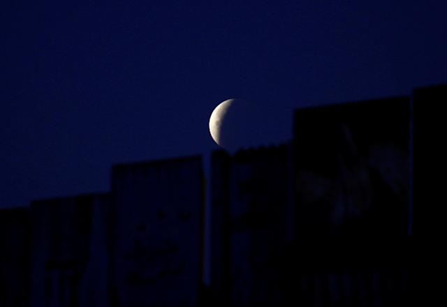 "<p>A ""Super Blue Blood Moon"" rises during a lunar eclipse in this picture taken from the Mexican side of the U.S.-Mexico border in Tijuana, Mexico, Jan. 31, 2018. (Photo: Jorge Duenes/Reuters) </p>"