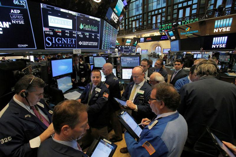 FILE PHOTO: Traders work on the trading floor at the New York Stock Exchange (NYSE) in Manhattan, New York