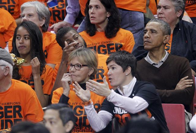 U.S. President Barack Obama (R) with his daughter Malia (L) attends the game between Princeton and Green Bay for the 2015 Women's NCAA Basketball Tournament at the XFINITY Center in College Park, Maryland March 21, 2015. Obama's niece Leslie Robinson plays for Princeton. REUTERS/Yuri Gripas