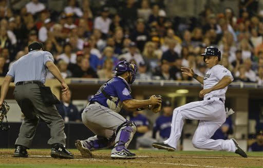 San Diego Padres' Will Venable slides into home where Colorado Rockies catcher Wilin Rosario waits to make the tag on a failed squeeze play in the seventh of a baseball game in San Diego, Tuesday, July 9, 2013. The umpire is Chris Guccione. (AP Photo/Lenny Ignelzi)