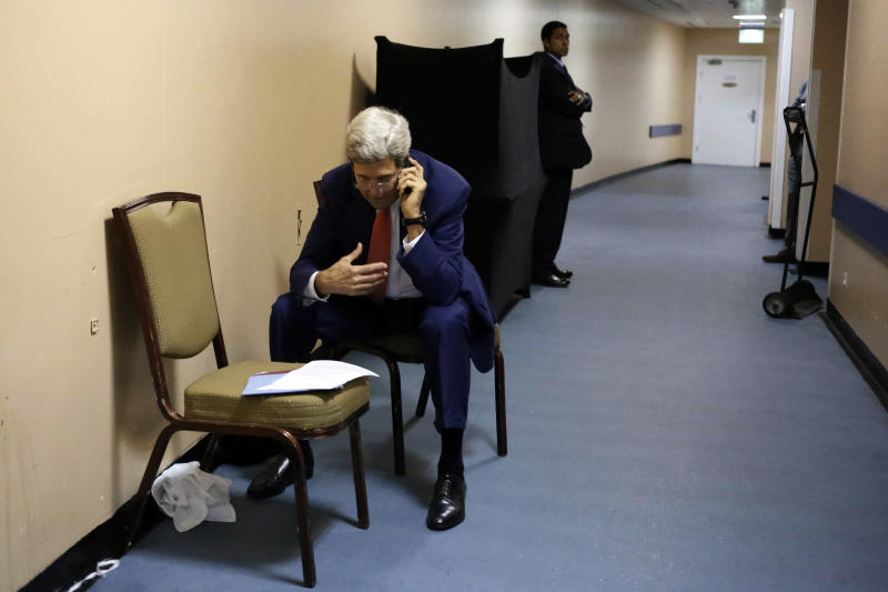 US Secretary of State John Kerry speaks on the phone with Qatar's Foreign Minister Khaled al-Attiya on July 25, 2014, from a hallway in a hotel in Cairo (AFP Photo/)