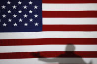 Democratic presidential candidate former Vice President Joe Biden casts a shadow on a flag as he speaks during a community event, Wednesday, Oct. 16, 2019, in Davenport, Iowa. (AP Photo/Charlie Neibergall)
