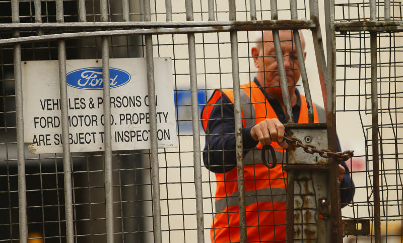 A security guard locks a gate after workers left the Ford Transit Assembly Plant in Southampton, England after being told that the site will close with the loss of up to 1,500 jobs Thursday Oct. 25, 2012. Ford, which expects to lose more than $1 billion a year in Europe, has been pursuing plant closures and layoffs. Fears were mounting that the axe may also soon fall in Britain as trade unions at Ford's Southampton plant have been called in for a meeting with management on Thursday. (AP Photo/Chris Ison/PA) UNITED KINGDOM OUT