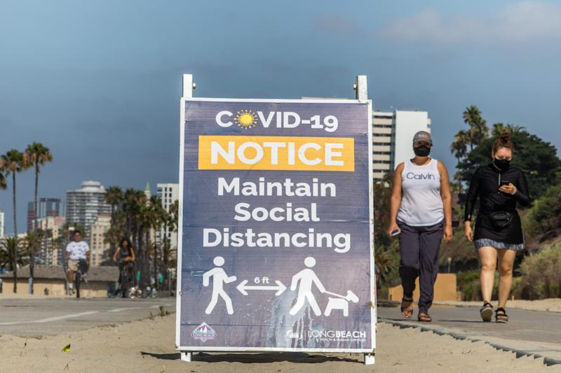 Women wearing facemasks walk near a notice about maintaining social distance on the beach in Long Beach, California, on July 14, 2020. - California's Governor Gavin Newsom announced a significant rollback of the state's reopening plan on July 13, 2020 as coronavirus cases soared across America's richest and most populous state. (Photo by Apu GOMES / AFP) (Photo by APU GOMES/AFP via Getty Images)