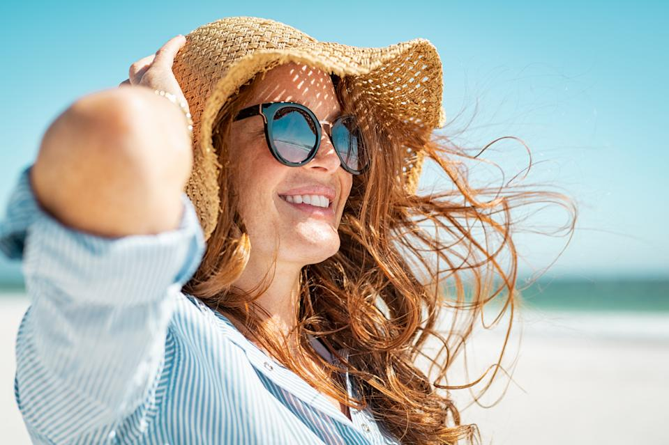 Side view of beautiful mature woman wearing sunglasses enjoying at beach. Young smiling woman on vacation looking away while enjoying sea breeze wearing straw hat. Closeup portrait of attractive girl relaxing at sea.