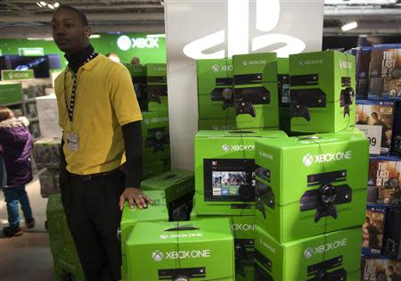 """A security guard stands beside a pile of XBOX One video game consoles at a Toys """"R"""" Us store during their Black Friday Sale in New York November 28, 2013. REUTERS/Carlo Allegri"""